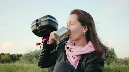 kupa : Portrait of a young Caucasian woman with a metal mug in her hand drinking a hot drink. Traveler motorcyclist with coffee on the cliff. Tourist relaxes in nature on the background of a motorcycle