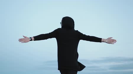 osamělost : Fashionable young Caucasian guy in a black cardigan with a hood admires nature and fresh air. A man in sunglasses spins with his arms outstretched against a cloudy evening sky. Travel concept Dostupné videozáznamy