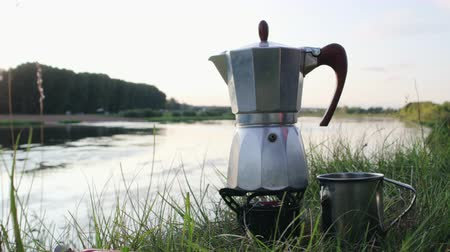 kupa : Geyser coffee maker with a metal mug is heated on the burner of a multi-fuel Primus on the background of a pond. Breakfast in an open summer camp on the river. Travel concept