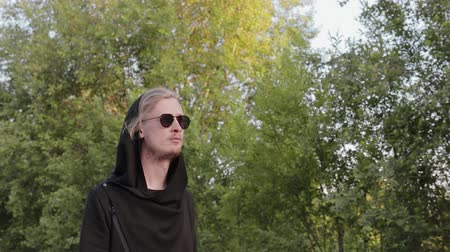 arka görünüm : A young handsome man in a stylish black cardigan and sunglasses is walking through the woods outdoors. Cute model guy enjoys a vacation in the country Stok Video