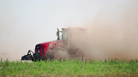 arbeidsomstandigheden : Side view agricultural tractor prepares dusty soil affected by drought. Concept of crop failure with soil erosion and agriculture Stockvideo