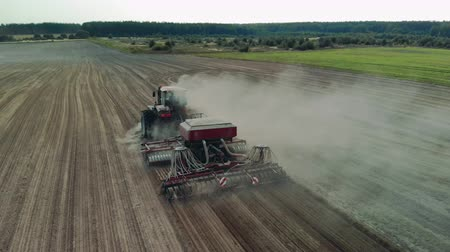 solo : Aerial cinematic shot of an energy-saturated tractor with a soil-cultivating sowing unit producing cultivation of poor arid farmland. Huge clouds of sand and dust. Rear view from the drone Stock Footage