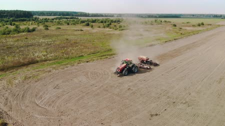 solo : Aerial cinematic shot of an energy-saturated tractor with a soil-cultivating sowing unit producing cultivation of poor arid farmland. Huge clouds of sand and dust. Side view from the front