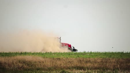 leveling : Side view agricultural tractor prepares dusty soil affected by drought. Concept of crop failure with soil erosion and agriculture Stock Footage