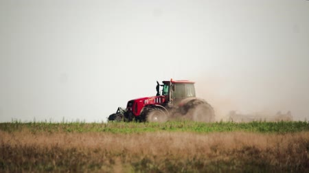 podmínky : Side view agricultural tractor prepares dusty soil affected by drought. Concept of crop failure with soil erosion and agriculture Dostupné videozáznamy