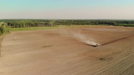 tırmık : A farmer sows the land on a tractor with a plow harrowing a large brown field in the spring season. A large cloud of dust forms behind the car. Concept of agriculture and agronomy