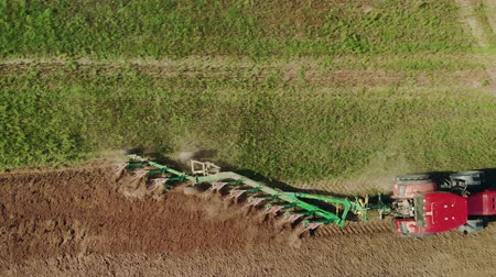 solo : Aerial top-down view from a birds eye view of a Tractor with a plow cultivating dark soil. Plowing the land with agricultural tools