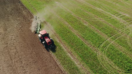 solo : Aerial view of farmer on a red tractor plowing dusty arid soil. The farm car is followed by hungry birds. Agribusiness in the spring