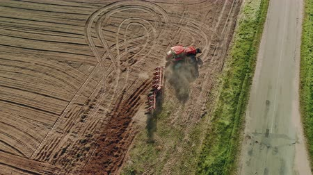 solo : Aerial view from top to bottom from a birds eye view of a tractor with a plow working the dark soil. Turn of the machine and turn of agricultural tools