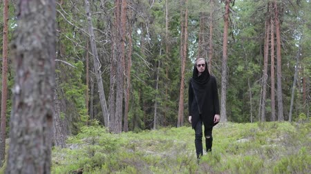 tek başına : Portrait of a young, cute guy in black clothes, who is walking through the woods in the open air, a sad concept of a man, he thinks about love, a broken heart of a girl, despair Stok Video