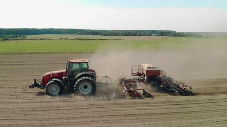 solo : Aerial view of a tractor with a combined seeding unit processing farmland in dry weather. The drone follows the side of the agricultural machine with clouds of sand and dust Stock Footage