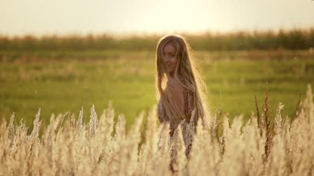 tahıllar : A beautiful, young, carefree girl with long blond hair walking through a wheat field at sunset. Butterflies fly over the spikelets on a warm summer evening. She turns, smiles, and looks at the camera. The concept of a happy person
