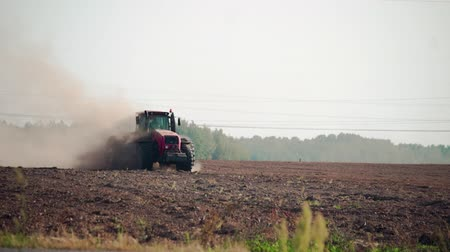 şartlar : Agribusiness: a farmer on an energy-intensive tractor plows arid, dusty soil in hot, dry weather. The agricultural machine is followed by a lot of wild birds in search of food, earth insects, worms