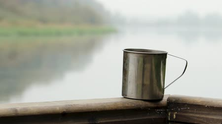 kupa : An aluminum mug stands on a wooden railing on the veranda with a hot drink on the background of a beautiful landscape of a lake with a forest. Steam escapes from the Cup. The concept of a weekend or camping Stok Video