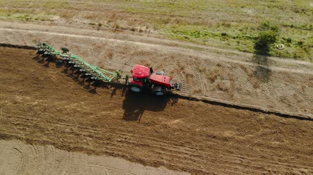 furrow : Top view of a farmer on a modern tractor with a revolving multi-field plow on the arable land processing the field. Preparing fertile soil for planting vegetables. The concept of agribusiness