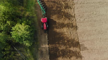 polska : Aerial view of a farmer in a modern tractor cultivating the soil for sowing with a trailer plow on support wheels with many ploughshares Wideo