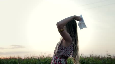 zabawka : A beautiful, young girl with long hair launches a paper airplane into the open air, which is pointed nose-first. Make a wish and let the plane go. The concept of follow your dreams Wideo