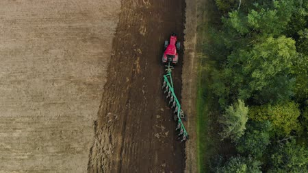 verimlilik : Aerial view of a farmer in a modern tractor cultivating the soil for sowing with a trailer plow on support wheels with many ploughshares. Drone takes off from the top of the object