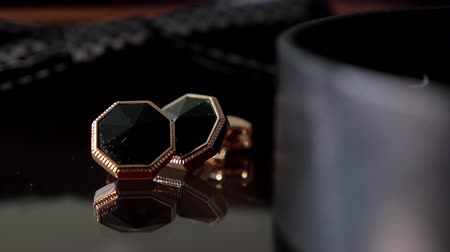 детали : Gold cufflinks with a black stone lie on a wooden table. With proper lighting, they Shine and reflect. Accessory for a businessman or groom Стоковые видеозаписи