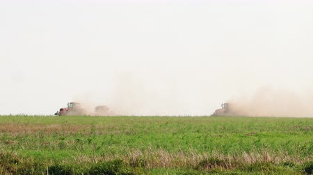 sow : Two tractors in the dust ride on farmland. Land cultivation and seed sowing in dry weather. The nutrition of birds. Environmental damage, soil erosion. Camera panorama