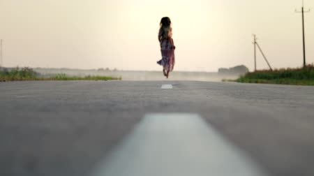 боке : Rear view of a beautiful, slender, young girl with long flowing hair running barefoot on an asphalt road. Slow-motion shot of a woman in a flowing dress at sunset Стоковые видеозаписи