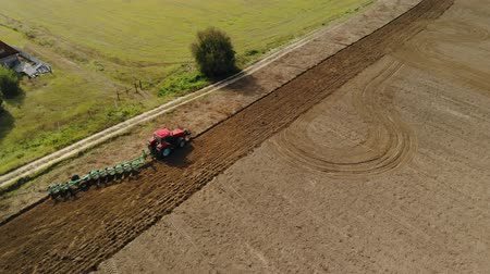 solo : The red tractor uses a seeder-cultivator to prepare the soil in early spring. Agricultural work on large, fertile land. Top view from the drone. Beautiful picture, the texture of the dark field and green grass