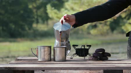 kupa : The hand of a tourist opens the lid of a geyser coffee maker, which stands on a gas burner against the background of the forest, in order to drink delicious coffee. Theme of tourism, Hiking and traveling in nature Stok Video