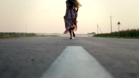 gevşek : Rear view of a beautiful, slender, young girl with long flowing hair running barefoot on an asphalt road. Slow-motion shot of a woman in a flowing dress at sunset Stok Video