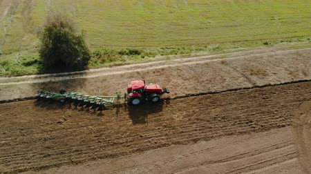centeio : Aerial shot: side view of a farmer on a red tractor processing farmland with a reverse plow with support wheels. Agricultural machine on the background of a field with a Bush. Concept of agribusiness