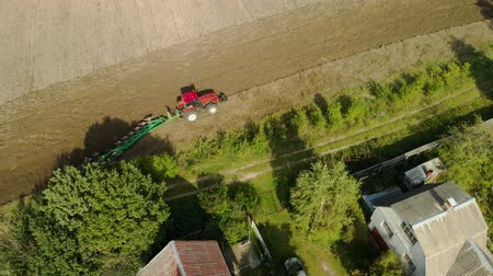sowing : Aerial: tractor with a plow on farmland near the village. The agricultural machine processes the soil for sowing seeds close to the village. Agribusiness on food products Stock Footage