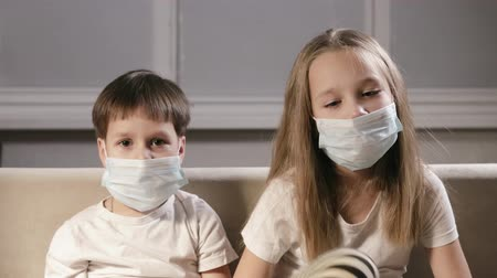 щит : Average plan of two children in the clinic in respiratory masks. Sad boy and girl sitting in protective equipment in the isolation ward of an infectious diseases hospital. Concept of fighting viruses
