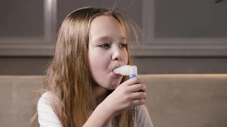 ar : Cute blonde girl baby breathes through a tube of steam with medication from an inhaler. Prevention of increasing immunity, fighting viruses at home