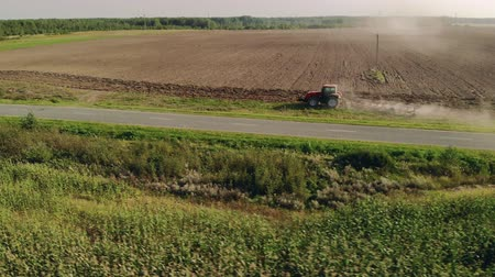 plough land : Aerial: tractor with a device processes the soil near a rural road for sowing on a Sunny summer evening. Plowing and cultivation of dusty land. The camera follows the side of the object