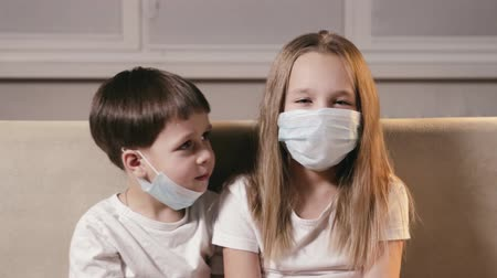 respiração : Sad funny children, a boy and a girl put respiratory masks on their mouths and noses. The concept of protection from SARS. Isolation of infected people