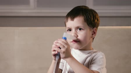 şartlar : Cute boy with kind eyes inserts a nebulizer nozzle into his nose and inhales for a runny nose. The child is treated for the disease at home. The concept of prevention of SARS Stok Video