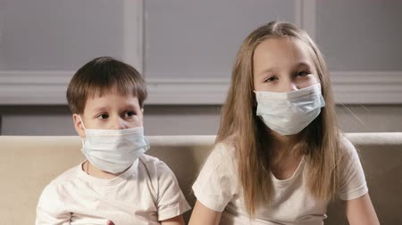 щит : Brother and sister wear medical masks on their faces because they dont want to get infected with a viral infection. The children are in the hospital and are being tested