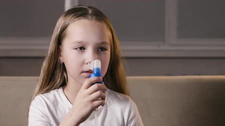 ar : Pretty, kind girl inserts a nebulizer nozzle into her nose and inhales for a runny nose. The child is treated for the disease at home. The concept of prevention of SARS