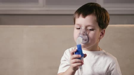 respiração : Cute funny boy breathes deeply through a nebulizer mask with medication to treat an infection. Inhalation the lungs of people in the home. Concept of medicine and health Vídeos