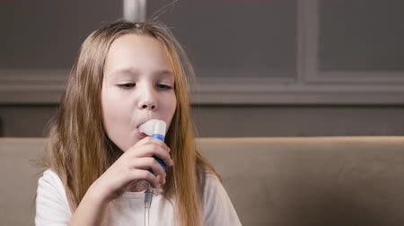 respiração : A small, pretty girl makes inhalations with a nebulizer at home. A sick child breathes through a spray bottle. Concept of treatment of childrens respiratory and lung diseases Vídeos
