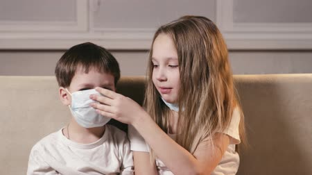 loved : Small, sick children in medical masks are examined for a viral infection, the sister puts on a mask to her brother, taking care of loved ones