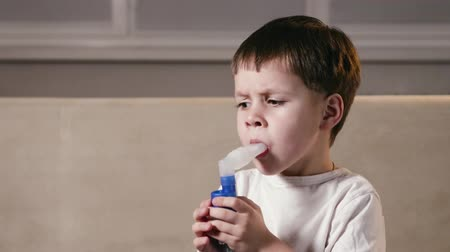 respiração : A small, cute boy makes inhalations using a nebulizer at home. A sick child breathes through a spray bottle. Concept of treatment of childrens respiratory and lung diseases Vídeos