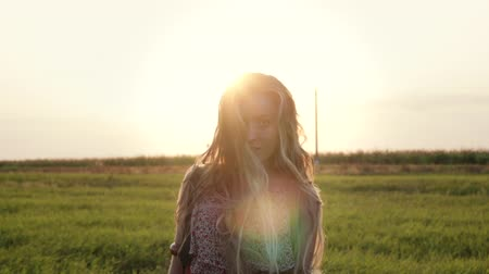 hippie : Front view of a pretty young hippie woman with a camera on her shoulder walking through an agricultural field at sunset and touching her long hair. Girl in a sundress in nature, handheld slow motion Stock Footage