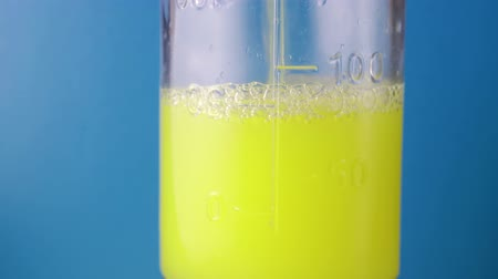 farmacologia : A yellow liquid is poured into a measuring flask on a blue background. Experiments with chemicals in test tubes and flasks. The concept of laboratory study Stock Footage