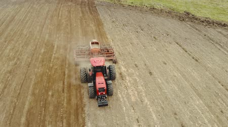 tahıllar : Aerial photography of a tractor with trailer equipment for sowing grain crops, the process of planting seeds in the ground as part of early spring agricultural work