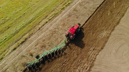 ranč : Aerial view of a circle of red tractor with a multi-plow preparing the soil for sowing on farmland in Sunny weather in spring and autumn. Modern agribusiness
