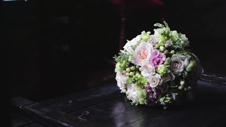 buquê : Stylish, wedding bouquet of flowers in light shades, which lies on a vintage, dark table on a black background. The concept of celebration and fun