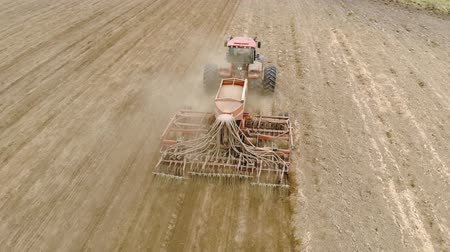 tahıllar : Aerial: rear view of an energy-saturated tractor with a trailed seed-tillage unit on support wheels that prepares the soil and sows grain in the spring. Telescopic coverers cover crops