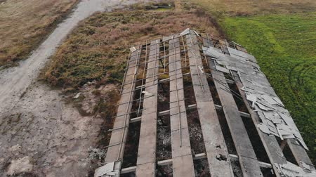 abandonné : Aerial: flying over an abandoned farm in the countryside due to the financial crisis. Destroyed roof of the cowshed in the barnyard. Unprofitable agribusiness in the livestock sector