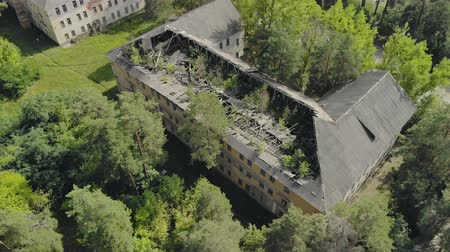 raam : Aerial: flying around an old abandoned concrete house in a Park. The buildings slate roof and rafters have collapsed, and trees are sprouting through the structure. The concept of chaos