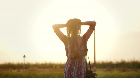 zatáčka : Lifestyle: portrait of a brown-haired woman in a floral print dress with a SLR camera on a shoulder strap in a field with high dry grass at sunset. Slow motion of a hipster girl posing